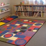 Picture of a colorful, geometric rug, surrounded by shelves holding board books and picture books.