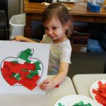 Little girl showing her tissue paper apple craft.