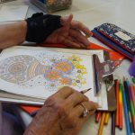 Adult woman's hands coloring a flower coloring sheet with a colored pencil.