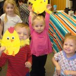 Children showing off their baby chick craft.