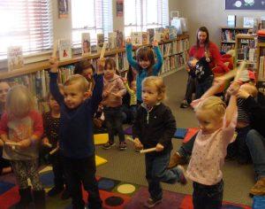 Children and parents tapping rhythm sticks.
