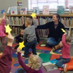 Children and parents holding yellow paper stars in the air.