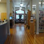 Looking down the main aisle of the library towards two chairs in front of the windows.
