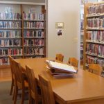 Library table and chairs surrounded by bookshelves holding adult fiction and biographies.
