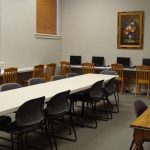 Meeting room with tables, chairs, and laptop computers for public use.