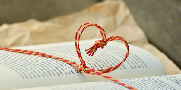 Heart shaped twine sitting on top of an open book with brown wrapping paper in the background.