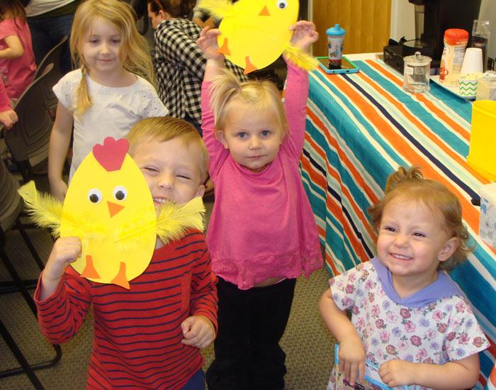 Children showing off their baby chick craft.