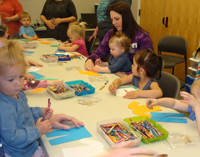 Children and parents coloring during craft time.