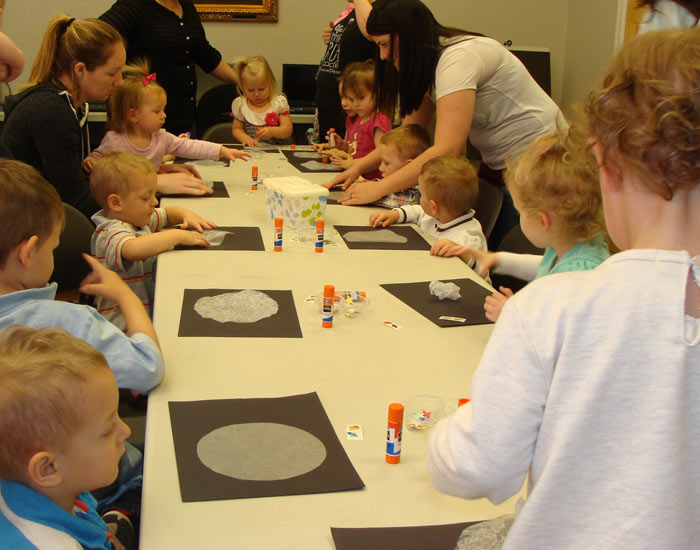Children and parents making a moon craft.