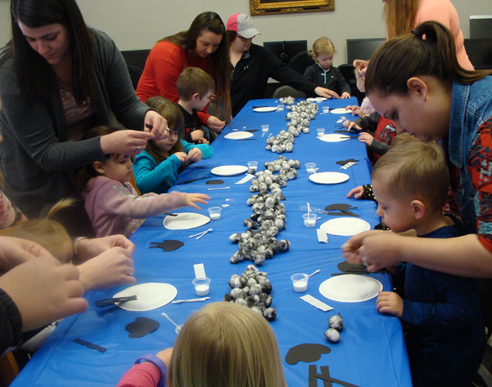 Children and parents making a sheep craft.