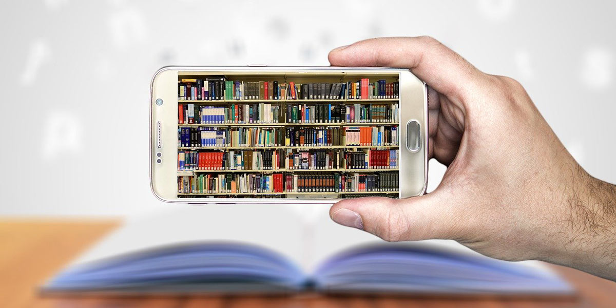 Hand holding a cell phone displaying a picture of library shelves with an open book in the background.