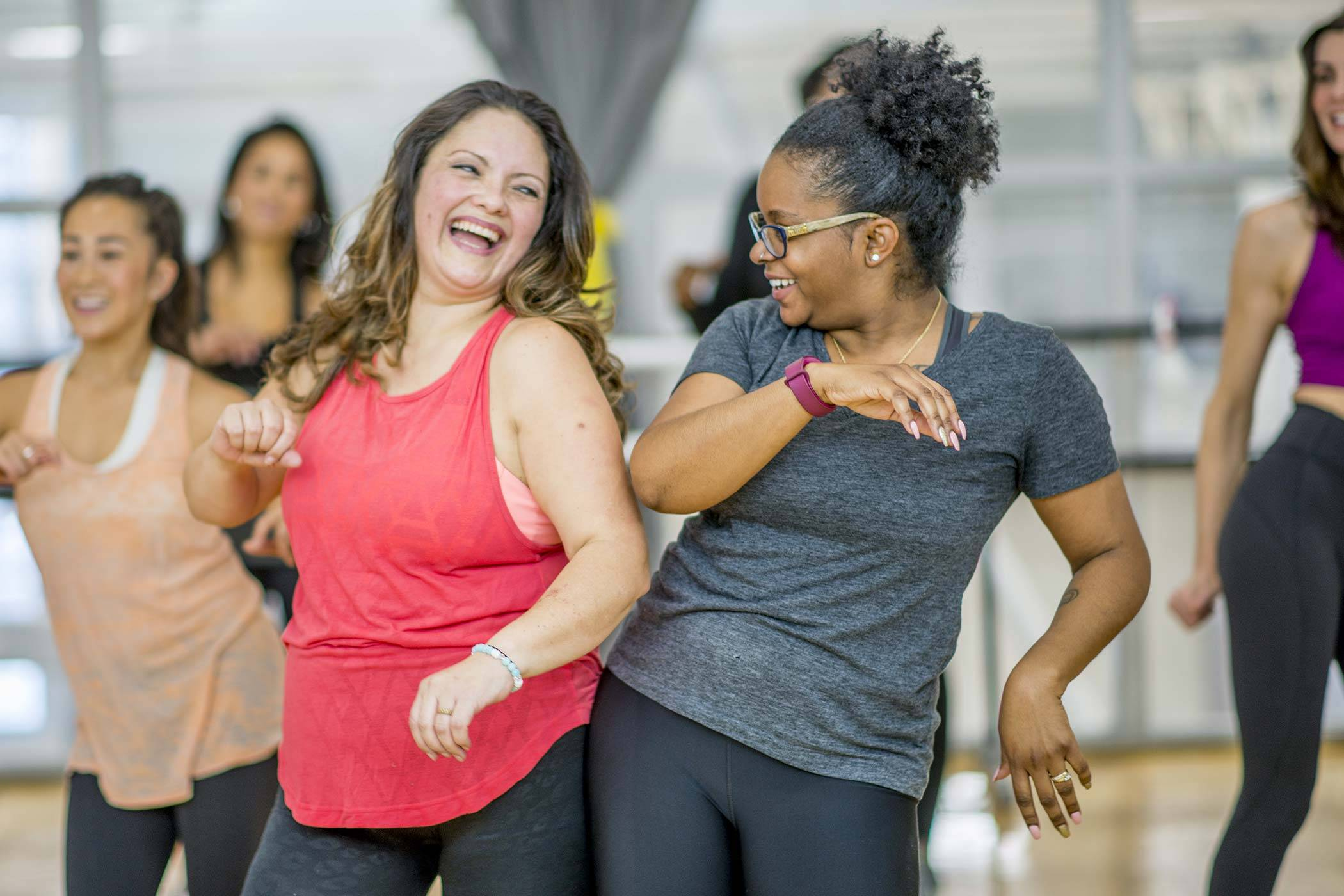 Ladies laughing while at an exercise class.